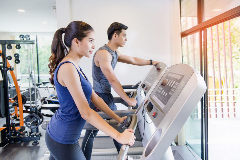 Man and women working out in gym together Togetherness Friendship Fitness Fitness Training Running Treadmill Activity Adult Females Males  Happiness Teamwork Couple Lifestyles Healthy Healthy Lifestyle Success Sport Cardio Trainers People Asian  Relaxing