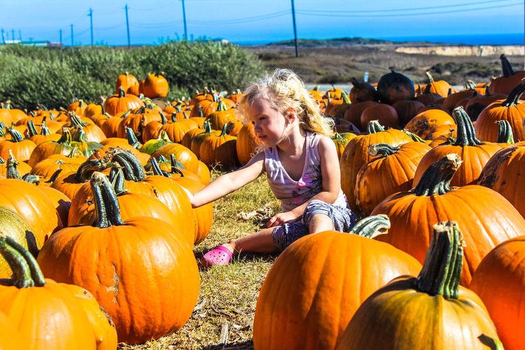 Full length of girl on pumpkin field