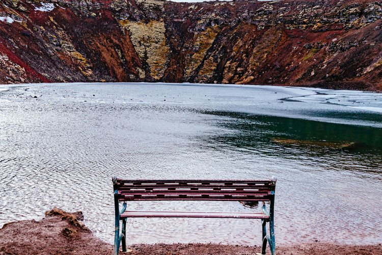 High Angle View Of Empty Bench At Frozen Crater Lake