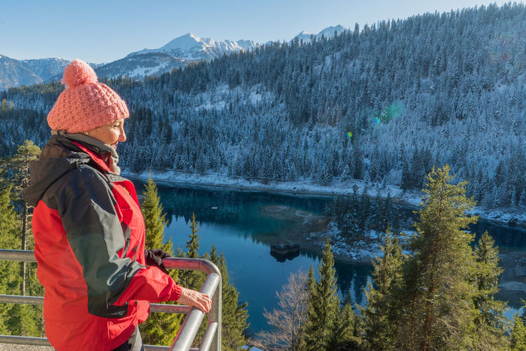 Woman Looking At View While Standing On Observation Point By Lake Against Mountain During Winter