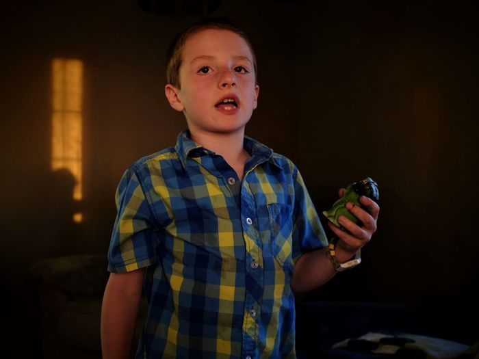 Boy holding toy animal at home