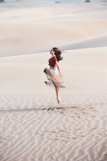 Woman dancing on sand at beach