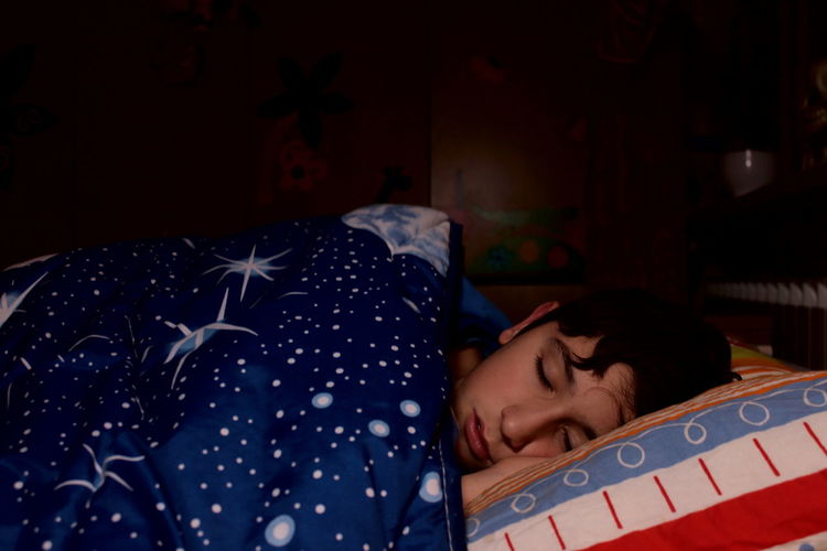 A caucasian boy sleeps in the bed of his bedroom covered by a quilt with a spatial motif