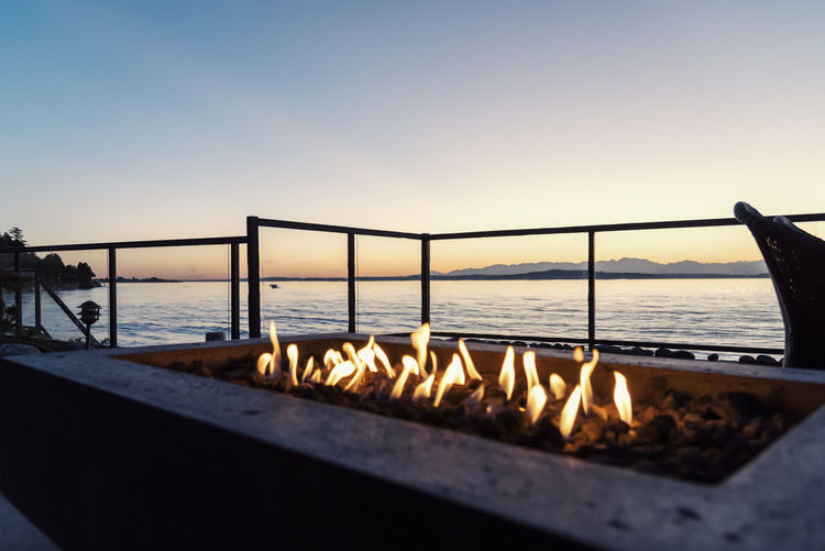 Backyard gas lit fire pit at sunset by the sea. Entertaining Fire Pit Flames Gas Natural Beauty In Nature Close-up Design Energy Evening Focus On Foreground Heating Horizon Horizon Over Water Landscape Nature No People Outdoors Scenics Sea Sky Sunset Water