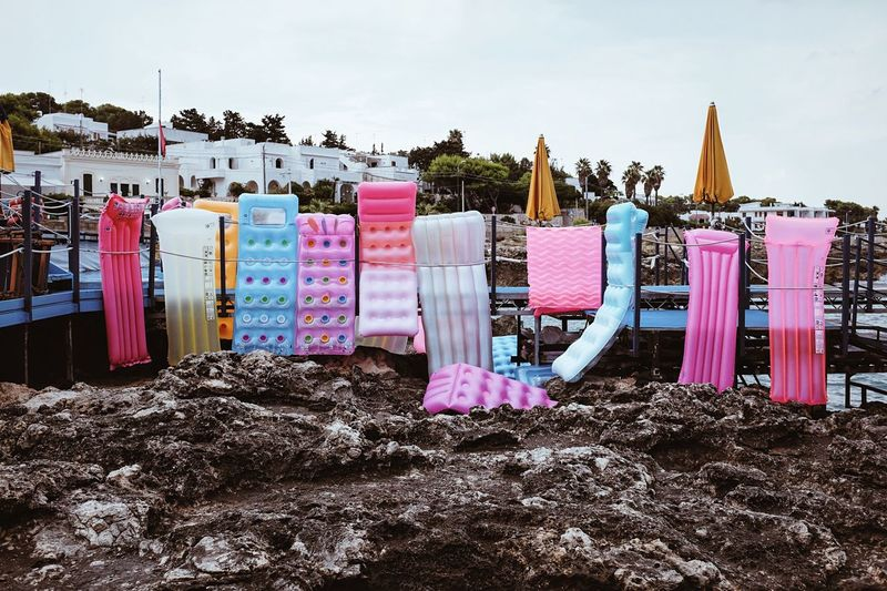 Pool rafts at beach against clear sky