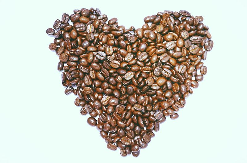 Close-Up Of Coffee Beans Arranged In Heart Shape Over White Background