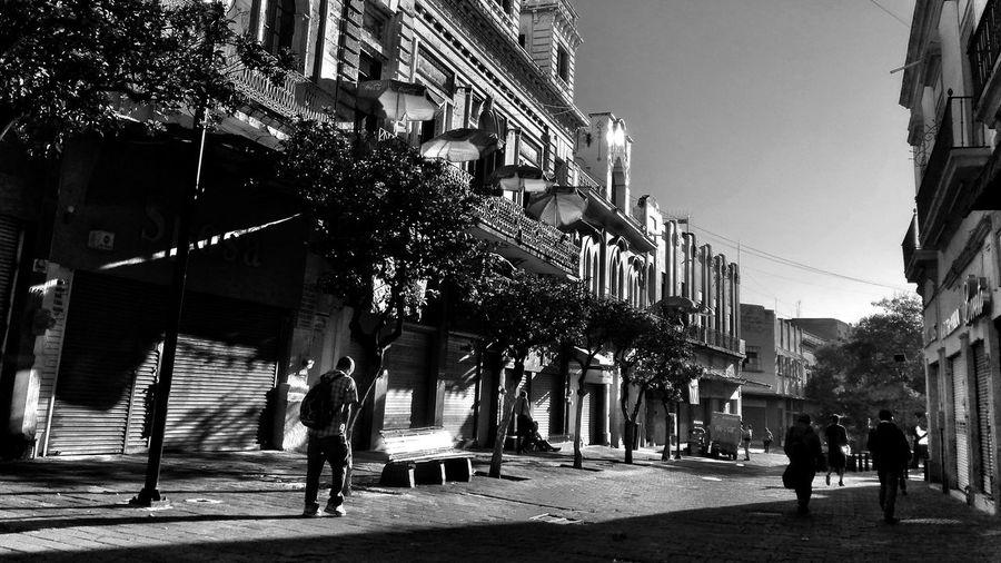 People walking on footpath amidst buildings