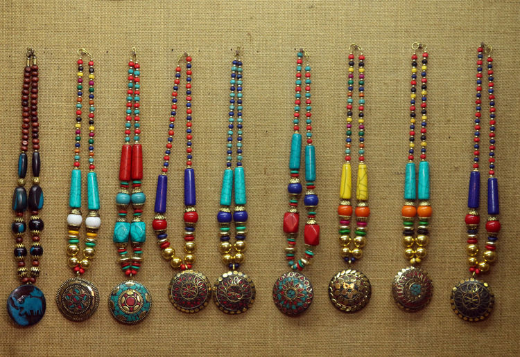 Close-up of colorful necklace hanging on wall for sale
