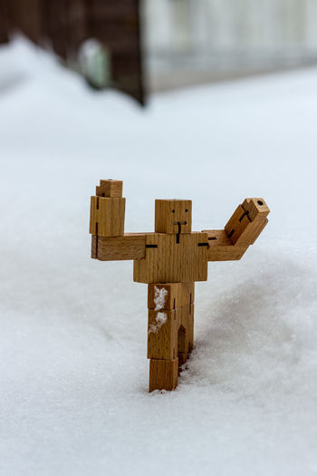 Close-up of wooden figurine on snow