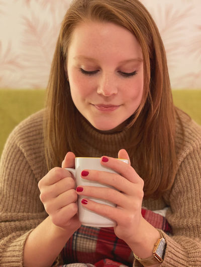 Close-up of a young woman drinking coffee cup