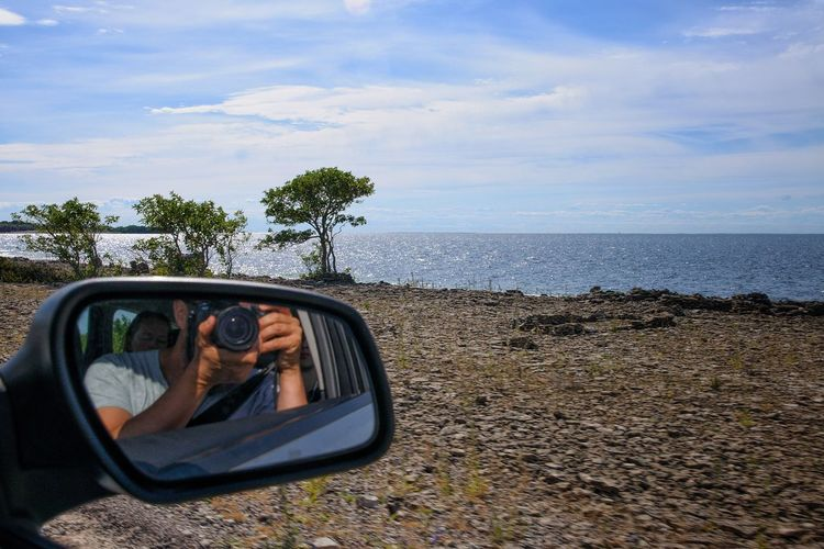 Reflection Of Man Photographing With Woman In Side-View Mirror Of Car