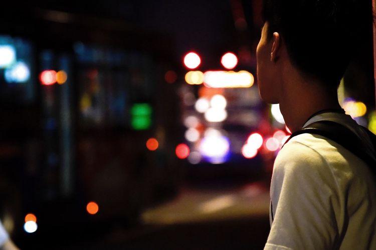 Rear View Of Man Looking At Illuminated Street