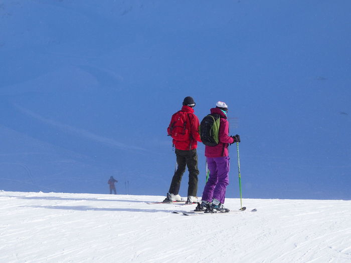 Rear View Of People Skiing On Snowcapped Mountain