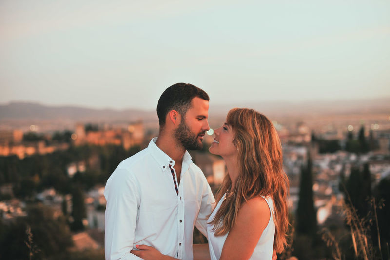 Happy romantic couple kissing against city during sunset