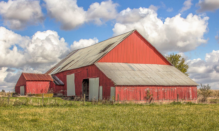 A beautiful red barn on a gorgeous autumn day. Cloud - Sky Built Structure Sky Architecture Field Land Grass Building Exterior Nature Agricultural Building Landscape Building Outdoors Farm Barn Weathered Picturesque Country Life Countryside Americana Pastoral Red Barn Country Scene Rustic Rural Scene Red