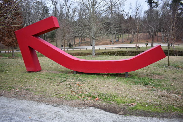 Big Red Arrow Day Giant Arrow Grass Nature No People Outdoors Park - Man Made Space Playground Red Red Arrow Tree