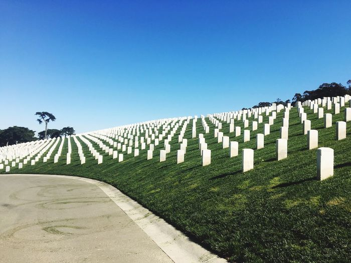 Low Angle View Of Tombstones In Cemetery Against Clear Blue Sky