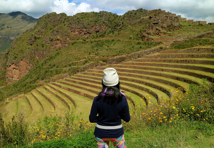 Female tourist admiring the Inca ancient agricultural terraces at Pisac Archaeological Site, Sacred Valley, Cusco region, Peru Pisac Cusco Archaeological Sites Archaeological Site Agricultural Field Terraced Field Rear View One Person Landscape Mountain Beauty In Nature Lifestyles Scenics - Nature Hat Land Leisure Activity Plant Environment Field Day Agriculture Nature Farm Outdoors Women International Women's Day 2019