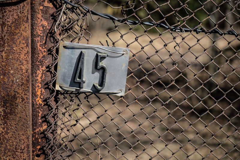 Close-up of arrow symbol on chainlink fence