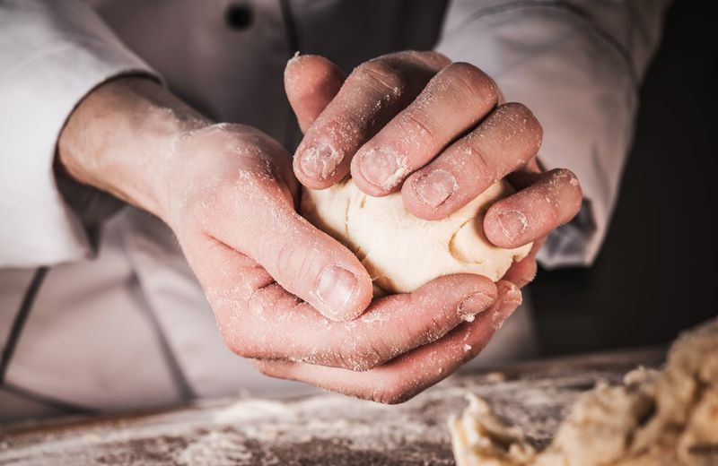 Midsection of chef kneading dough on table