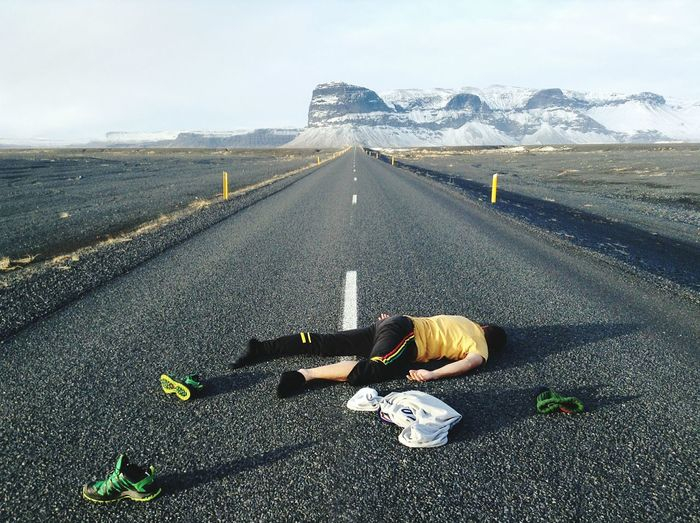 Man Lying On Country Road Along Landscape