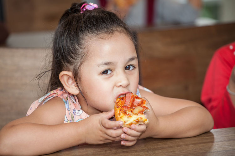 Portrait of cute girl eating pizza in classroom at school