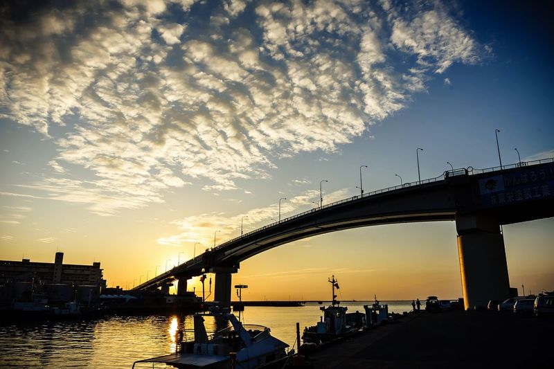 Low angle view of bridge over river against cloudy sky during sunset