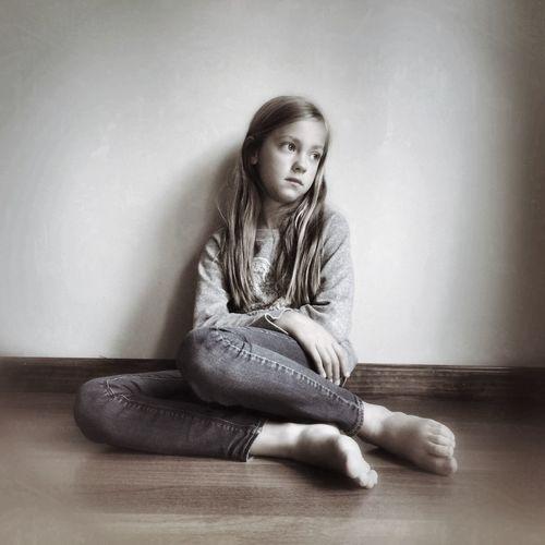 Full length of a sad girl sitting on floor against wall