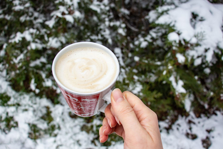 Hand holding coffee cup during winter