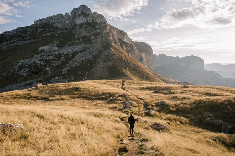 Rear view of man walking on land against mountain range and sky