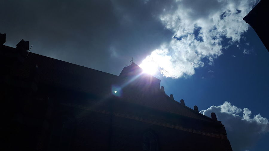 Low angle view of sunlight streaming through silhouette building against sky
