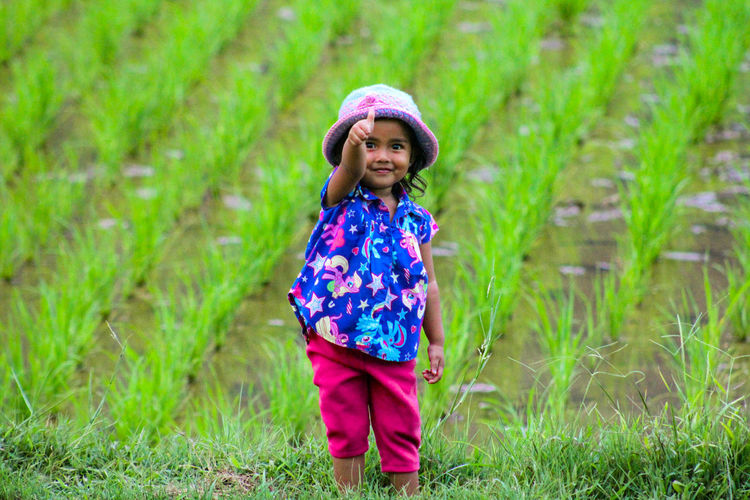 Portrait of girl standing on agricultural field