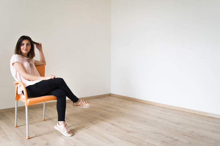 Full length portrait of young woman sitting on chair at home