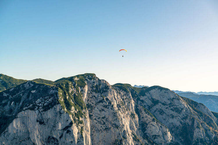Paragliding pilot flying above mountains in fall colors, altaussee, austria.