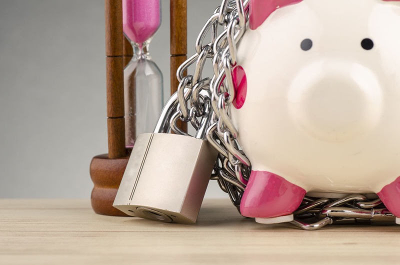 piggy bank surrounded by chains and padlock on wooden desk Indoors  No People Still Life Close-up Table Metal Chain Pink Color Thread Large Group Of Objects Finance Wood - Material Investment Business Representation Choice Personal Accessory Flooring Art And Craft