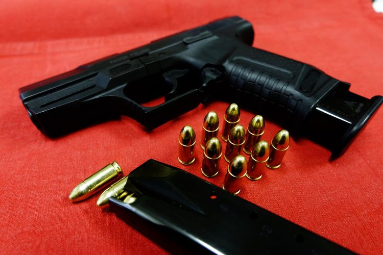 Close-Up Of Gold Bullets And Handgun On Table