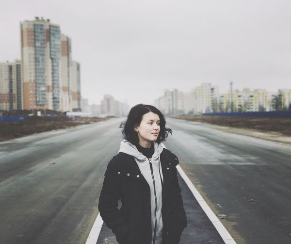 Young woman standing on road in city against clear sky