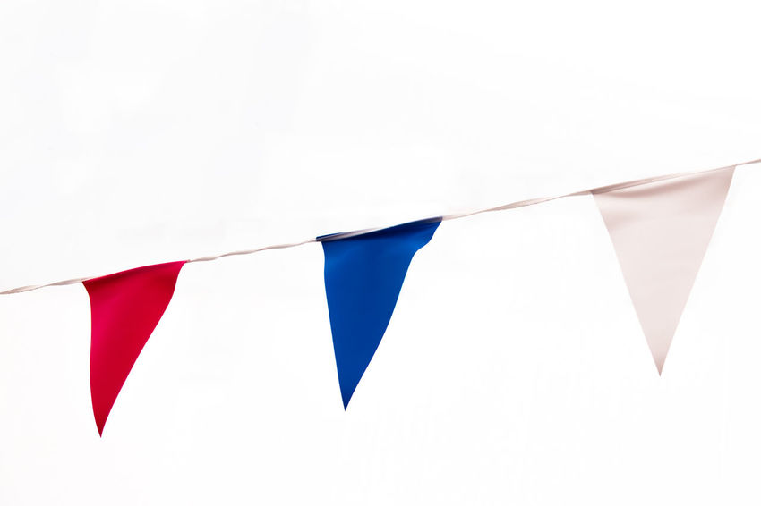 Red, white and blue bunting flags at a festival. Blue Flag Graphic Blue Bunting Bunting Flags Buntingflag Close-up Copy Space Day Decoration Flag Hanging In A Row Multi Colored No People Patriotism Pride Red Red Flag Rope Shape Triangle Shape White Background White Color White Flag