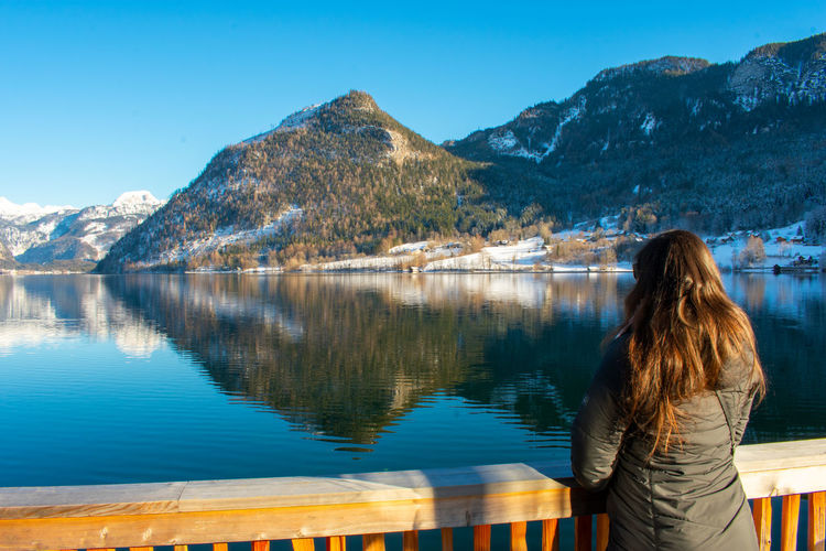Rear view of woman looking at lake against mountains while standing by railing