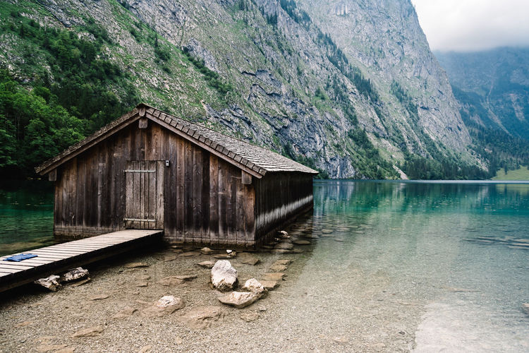 Built Structure By Lake Against Mountain