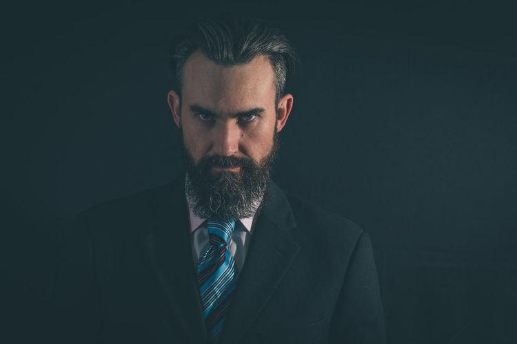 Portrait of serious businessman standing against black background