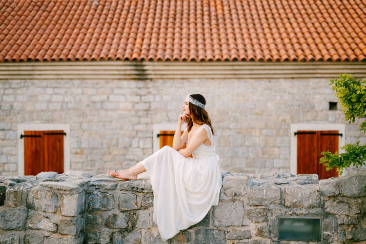 Side view of bride siting against house