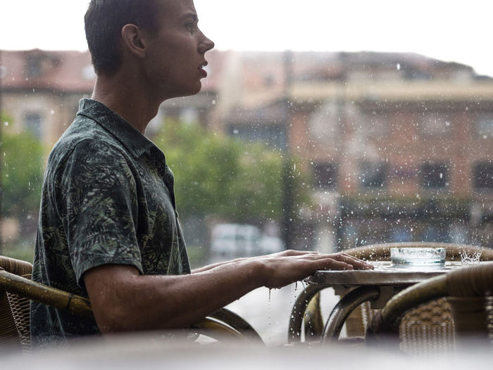 Side View Of Young Man Sitting At Sidewalk Cafe During Rain