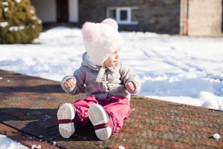 Full length of cute baby girl in snow