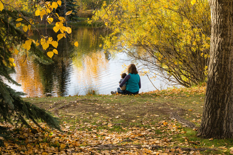 Rear view of mother and son relaxing by calm lake
