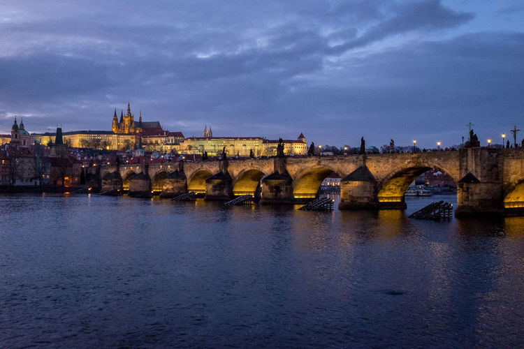 Illuminated charles bridge over vltava river by st vitus cathedral at dusk