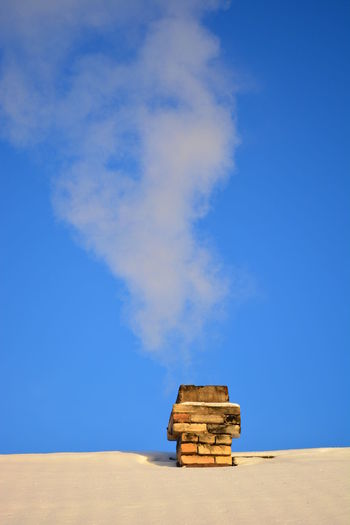 Low angle view of smoke stack on snow covered roof