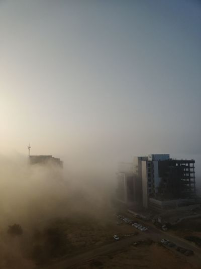 High angle view of buildings against sky in foggy weather