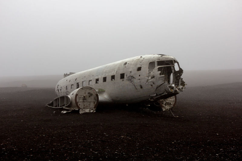 Abandoned airplane on land during foggy weather
