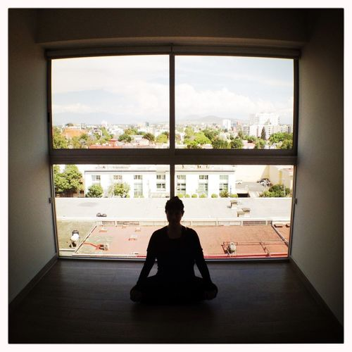 A woman doing yoga exercises in her modern living room. Woman Exercise Meditation Yoga Pilates Mexico City Window Cityscapes View Crosslegs